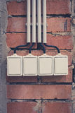Gruppe von vier Lichtschaltern auf Backsteinmauer stockbilder