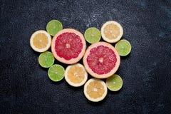 Gruppe von Zitronen, von Kalken und von Pampelmuse auf dunklem Hintergrund stockfotos