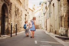 Gruppe von zwei Kindern, die auf die Straßen der alten europäischen Stadt gehen stockfotografie