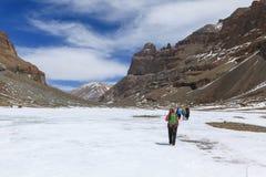 Gruppe Wanderer gehen auf den gefrorenen Fluss auf dem Weg zu Kailash-Berg, Tibet Stockfoto