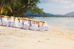 Gruppe weiße Abdeckungsstühle mit Goldschärpe auf dem Strand während der Hochzeitsortvorbereitung Lizenzfreies Stockfoto