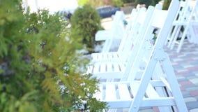 Gruppe weiße Klappstühle gründete für eine Hochzeitszeremonie im Freien stock video