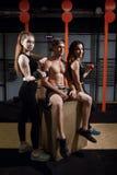 Gruppe weibliche und männliche Erwachsenen, die zusammen auf Kasten als gute Freunde in der Turnhalle sitzen stockbild