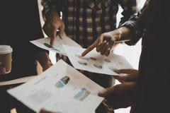 Gruppe Wirtschaftler bei der Sitzung Ideen besprechend während lookin stockfoto
