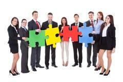 Gruppe Wirtschaftler, die Puzzlespielstücke halten Stockfoto