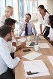 Gruppe Wirtschaftler, die um Tabelle im Büro sich treffen Lizenzfreie Stockfotos