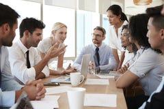 Gruppe Wirtschaftler, die um Tabelle im Büro sich treffen Stockfotografie