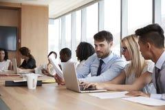 Gruppe Wirtschaftler, die um Tabelle im Sitzungssaal sich treffen Stockfotos