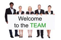 Gruppe Wirtschaftler, die Willkommen zu Team Placard halten stockbilder