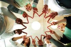 Gruppe Wirtschaftler, die zusammen Vzeichen zeigen Stockbild