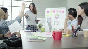 Gruppe zufällig gekleidete Geschäftsleute, die Ideen im Büro besprechen stock footage