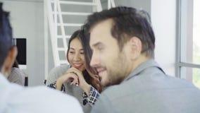 Gruppe zufällig gekleidete Wirtschaftler, die Ideen im Büro besprechen stock footage