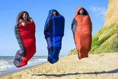 Gruppe zujubelnde Wanderer, die in Schlafsäcke auf der Küste springen Lizenzfreie Stockfotografie