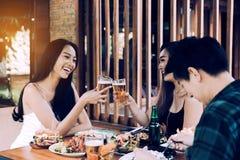 Gruppe zujubelndes Bier der asiatischen Leute an der glücklichen Stunde des Restaurants herein lizenzfreie stockfotos