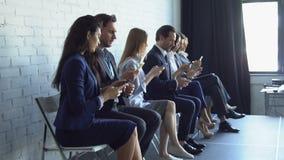 Gruppen av affärsfolk som använder cellen Smart, ringer maskinskrivningmeddelanden på moderna grejBusinesspeople som sitter i rad