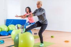 Gruppen av aktiva gladlynta sportiga kvinnor som gör enkla bensquats med jämvikt, klumpa ihop sig utbildning inomhus i idrottshal Royaltyfri Fotografi