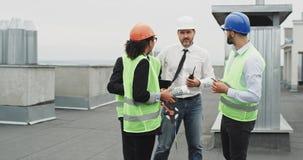 Gruppen av arbetare i affärsmän för en arkitekt för tekniker för konstruktionsplats har ett möte på taket av konstruktion stock video
