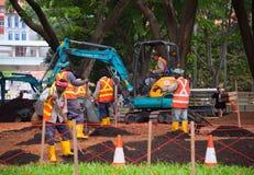 Gruppen av arbetare parkerar in Singapore Arkivbilder