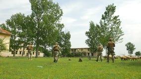 Gruppen av armén tjäna som soldat att patrullera i en övergiven inhysa skyddande och tjänande som arbetsuppgift för område stock video