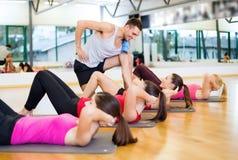 Gruppen av att le kvinnor som att göra sitter, ups i idrottshallen Arkivbild