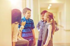 Gruppen av att le skolan lurar samtal i korridor royaltyfri foto