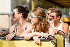 Gruppen av att le vänner som förbi reser, turnerar bussen Arkivfoton