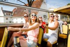 Gruppen av att le vänner som förbi reser, turnerar bussen Royaltyfria Bilder
