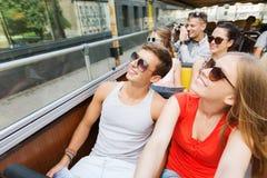 Gruppen av att le vänner som förbi reser, turnerar bussen fotografering för bildbyråer