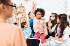 Gruppen av barn drar händer till frågan för svarslärare` s i grundskola för barn mellan 5 och 11 år royaltyfri bild
