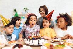 Gruppen av barn ska blåsa ut stearinljus på kakan lycklig deltagare för födelsedag arkivbild