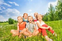 Gruppen av barn skrattar sammanträde på ett gräs Royaltyfri Foto