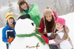 Gruppen av barn som bygger snowmanen skidar på, ferie arkivfoton