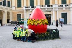 Gruppen av barn som framme tar fotoet av det stora röda påskägget Arkivbild