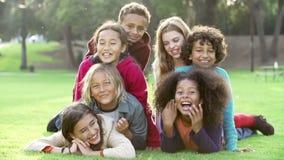 Gruppen av barn som ligger på gräs i, parkerar tillsammans stock video
