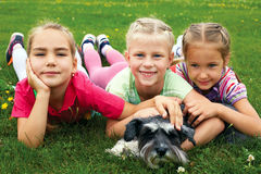 Gruppen av barn som spelar på grönt gräs i vår, parkerar Royaltyfria Bilder