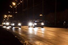 Gruppen av bilar rider staden på skymning Arkivfoto