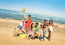 Gruppen av blandras- lyckliga vänner som har gyckel med stranden, spelar Arkivbild