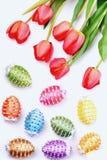 Gruppen av blommor nära dekorerade påskägg i olika färger Arkivfoton