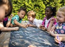 Gruppen av dagiset lurar vänner som utomhus drar konstgrupp Arkivfoto