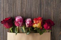 Gruppen av den flerfärgade rosen blommar i pappers- kuvert över träb Arkivbild