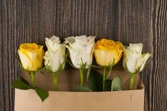 Gruppen av den flerfärgade rosen blommar i pappers- kuvert över träb Fotografering för Bildbyråer