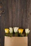 Gruppen av den flerfärgade rosen blommar i pappers- kuvert över träb Royaltyfria Foton