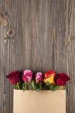 Gruppen av den flerfärgade rosen blommar i pappers- kuvert över träb Royaltyfri Foto