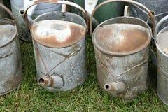 Gruppen av den gamla antikviteten galvaniserade järn som bevattnar cans på gräs arkivbilder