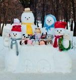 Gruppen av det olika formatet klädde snögubbear utomhus i vinter Arkivfoton