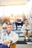 Gruppen av doktorer sitter i avbrott på trappa i klinik royaltyfria bilder