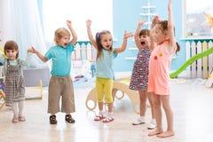 Gruppen av emotionella vänner med deras händer lyftte Ungar har rolig tidsfördriv i daycare arkivfoto
