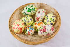 Gruppen av färgrika easter ägg dekorerade med blommor som gjordes av decoupageteknik, i en korg Arkivbilder