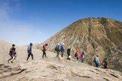 Gruppen av fotvandrare går i linje på berglutning Arkivfoton