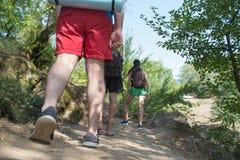 Gruppen av fotvandrare med ryggsäcken har en gå resa till och med skogen på en solig dag Royaltyfri Fotografi